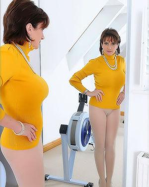 Зрелая женщина в лосинах стоит перед зеркалом 12 фото