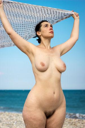 Голая женщина с широкими бедрами на пляже
