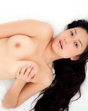 Красивая азиатка нежится на мягкой кровати 10 фото