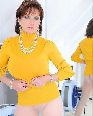 Зрелая женщина в лосинах стоит перед зеркалом 2 фото
