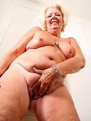 Пожилая развратная толстуха сильно увлечена мастурбацией на фото